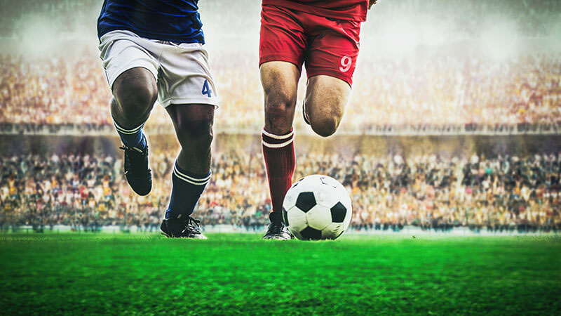 サッカーの試合でボールを追いかける選手