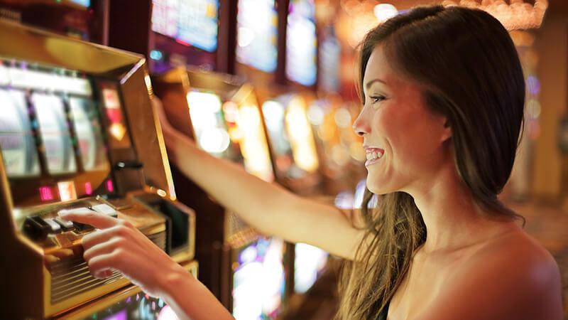 女の人がカジノスロットゲームで遊ぶ